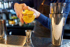 Bartender squeezing juice into jigger at bar stock photo