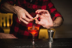 Bartender is squeezing orange peel into a cocktail glass stock images