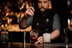 Bartender stirring alcohol with an ice cubes in the tall measuring glass cup with a spoon. On the bar counter on the blurred background royalty free stock photo