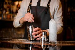 Bartender stirring an alcoholic drink in the steel shaker. With a spoon on the steel bar counter royalty free stock image