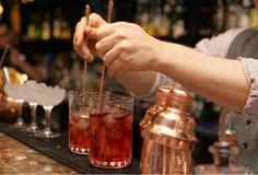 Bartender is stirring cocktails. On bar counter stock images
