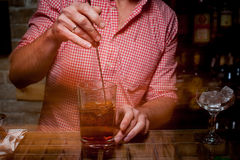 Bartender is stirring cocktails on bar counter Royalty Free Stock Photography