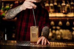 Bartender stirring a Lemonade cocktail with the spoon. In the glass on the bar counter royalty free stock photos