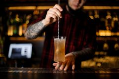 Bartender stirring with a spoon a yellow achoholic drink in a co. Cktail glass with ice on the bar counter stock image