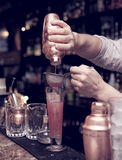 Bartender is straining cocktail Stock Image