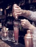 Bartender is straining cocktail Stock Image