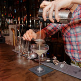 Bartender is straining drink in glass Stock Images