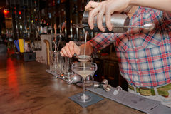 Bartender is straining drink in glass Stock Photography