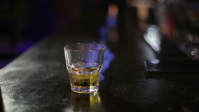 Bartender takes a glass of whiskey on the bar on the way out of the fire stock video