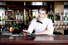 Bartender taking an order. Young smiling bartender taking an order Royalty Free Stock Photos