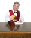 Bartender Tending Bar Serving Beer, Isolated. Happy, friendly, smiling bartender tending bar and serving beer. Isolated on white Stock Photography