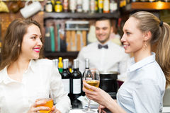 Bartender and two girls at bar Royalty Free Stock Images