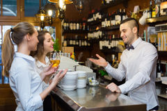 Bartender and two girls at bar Royalty Free Stock Photos