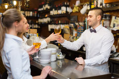 Bartender and two girls at bar. Young bartender and two smiling girls with wine at bar. Selective focus on guy stock photography