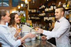 Bartender and two girls at bar Royalty Free Stock Photos