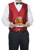 Bartender, Waiter, Server, Beer, Isolated. Waiter, bartender, server, serving beer. The man is dressed in a classy manner and is wearing a red vest and a bow tie Stock Image