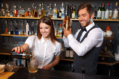 Bartender and a waitress in the bar. Portrait of a waitress wearing a white blouse pouring a cocktail from a shaker smiling and a handsome bartender mixing a Royalty Free Stock Photos