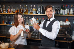 Bartender and a waitress during work. Portrait of a handsome bartender and a pretty waitress standing smiling holding a glass and wiping it standing in the bar Royalty Free Stock Image