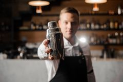 Bartender in white shirt and apron holding a shaker. On the background of shelves with bottles and bar counter stock photography