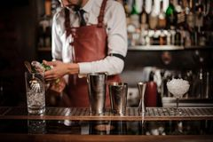 Bartender holding a bottle of alcoholic drink on the bar counter. Bartender in the white shirt and brown leather apron holding a bottle of alcoholic drink on the stock images