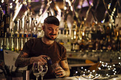 Bartender At Work. Hipster bartender is pouring drinks behind the bar Stock Photos