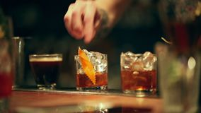 Bartender working. Adding decor element to an alcoholic cocktail in the glass. Mid shot stock footage