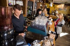 Bartender Working At Counter While Female Stock Photography
