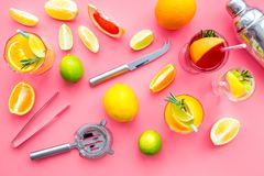 Bartender workplace for make fruit cocktail with alcohol. Shaker, strainer and other bar tools near citrus fruits and. Glass with cocktail on pink background stock photo