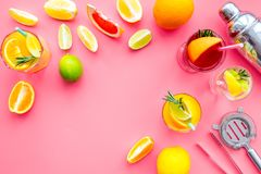 Bartender workplace for make fruit cocktail with alcohol. Shaker, strainer and other bar tools near citrus fruits and. Glass with cocktail on pink background stock photos