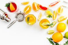 Bartender workplace for make fruit cocktail with alcohol. Shaker, strainer and other bar tools near citrus fruits and. Glass with cocktail on white background royalty free stock photo