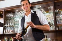 Bartenderanseende bakom bommar för med wine Arkivfoto