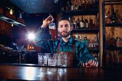 Bartenderbartender med en flaska av alkohol bak räknaren in arkivbilder