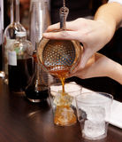 Bartenderen anstränger coctailen in i exponeringsglas Arkivfoton