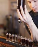Bartenderen fyller några exponeringsglas i en ro Royaltyfri Foto
