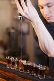 Bartenderen fyller några exponeringsglas i en ro Royaltyfri Bild