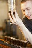 Bartenderen fyller några exponeringsglas i en ro Arkivbild