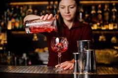 Bartenderflicka som häller en läcker ljusröd coctail arkivbild