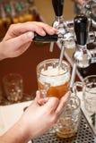 Bartenderhänder som häller ett utkast, tillverkar öl in i en råna royaltyfri bild
