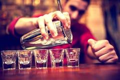Bartenderhand med den hällande drycken för skakablandare royaltyfri fotografi