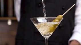 Bartenderhand som häller martini i ett coctailexponeringsglas i ultrarapid arkivfilmer