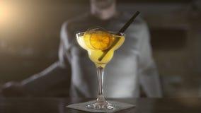Bartendern avslutar coctailen i högt exponeringsglas med torkade frukter och coctailsugrör som gör coctailar i en stång, alkohol lager videofilmer