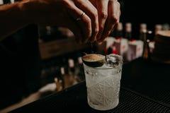 Bartendern dekorerar coctailen med citronen ingen framsida arkivfoto