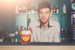 Bartendern erbjuder den exotiska kryddiga alkoholiserade coctailen Fotografering för Bildbyråer