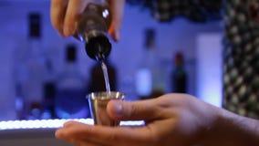 Bartendern förbereder den alkoholiserade coctailen hälla för alkohol lager videofilmer