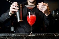 Bartendern f?rbereder margaritacoctailen, m?rk bakgrund, n?rbild arkivfoton