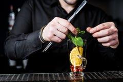 Bartendern f?rbereder fruktte med tranb?r i ett exponeringsglas, m?rk bakgrund arkivbild