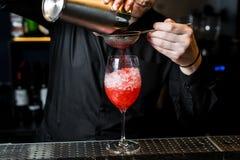 Bartendern f?rbereder margaritacoctailen, m?rk bakgrund, n?rbild fotografering för bildbyråer