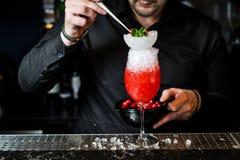 Bartendern f?rbereder margaritacoctailen, m?rk bakgrund, n?rbild royaltyfria foton
