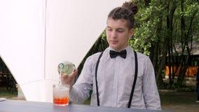 Bartendern gör den blandade drinken på bakgrundsnaturen, stångarbetaren som överträffas upp ROM-minne in i exponeringsglas med is lager videofilmer
