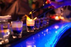 Bartendern gör den varma alkoholiserade coctailen och antänder stången elitnattklubben under partiet förbereder en brännhet cocta royaltyfria foton